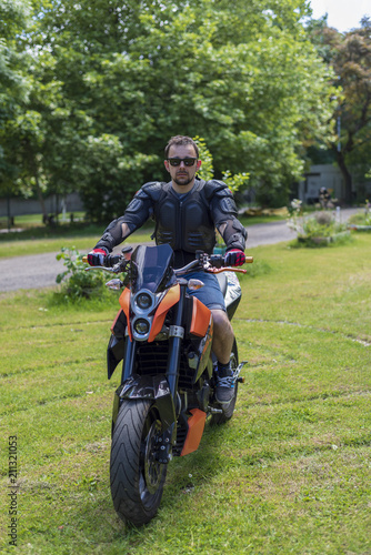 Biker In A Leather Jacket On A Black And Orange Motorcycle Poster