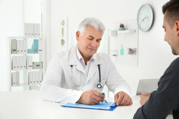 Senior male doctor working with client at reception desk in hospital
