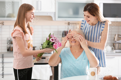 Fotografering  Young woman with daughter congratulating mature family member at home