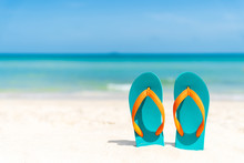 Flip Flop On Sandy Beach, Green Sea And Blue Sky Background For Summer Holiday And Vacation Concept.