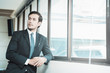 Portrait of handsome businessman standing near window in office.