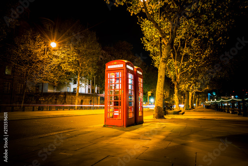 Fotografie, Obraz  Traditional red British telephone booth viewed at night in London