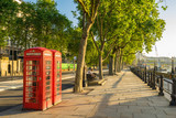 Fototapeta Londyn - A traditional red phone booth in London at sunny morning