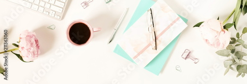 Flat lay women's office desk. Female workspace with laptop, flowers peonies, accessories, notebook, glasses, cup of coffee on white background. Top view feminine background.Copy space.banner