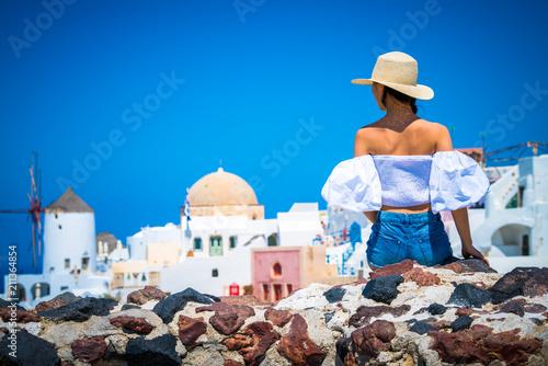 Female tourist exploring Oia village in Santorini, Greece Canvas Print