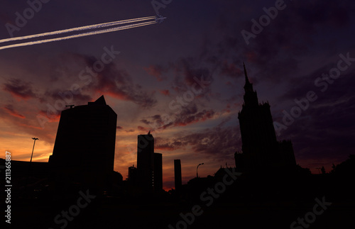 Foto op Canvas Stad gebouw View of the Palace of Culture in Warsaw at night and a flying plane