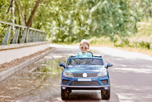 The Girl Is Having Fun Riding A Blue Electric Car In The Park. Toning.