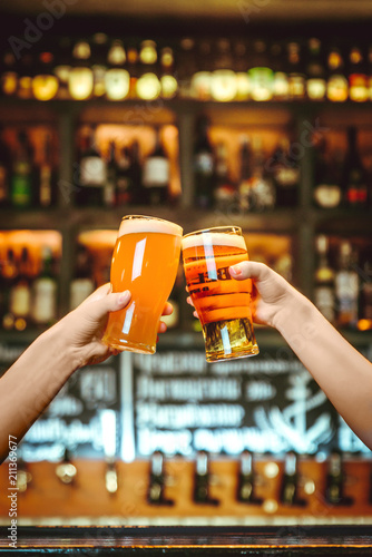 Two friends toasting with glasses of light beer at the pub. Beautiful background of the Oktoberfest. fine grain. Soft focus. Shallow DOF © qwasder1987