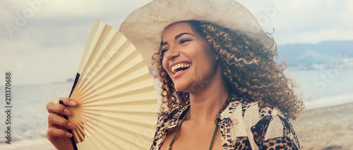 Fotografie, Obraz  Beautiful young woman smiling and holding fan on the beach, letterbox