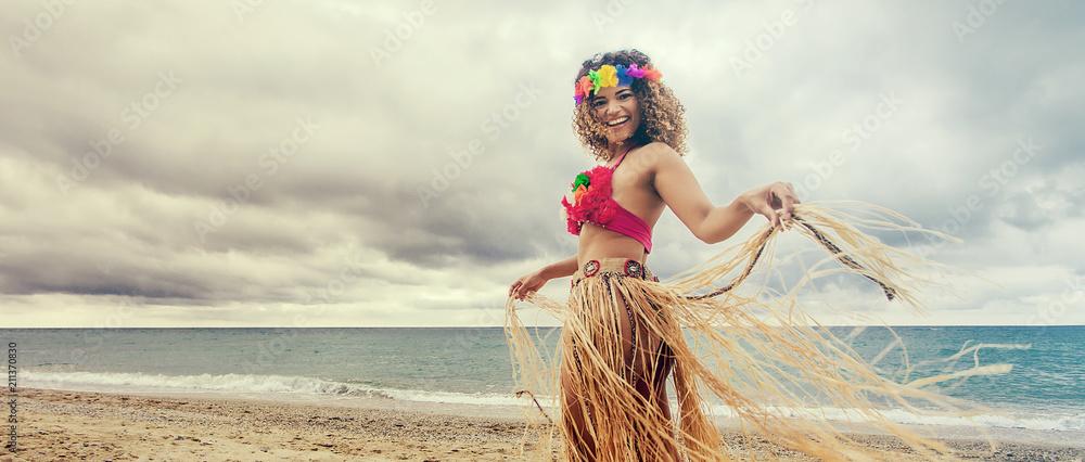 Fototapeta Happy and cheerful hawaiian woman portrait dancing on the beach, letterbox