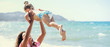Happy mother holding and playing with her daughter on the beach, letterbox