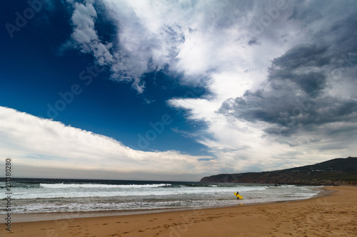 View of the Guincho beach near Atlantic coast. Surfer on the ocean coast in a wet suit with surfboard. Landscape of sunny day, blue sky and a mountain in distance. Cascais. Portugal.