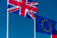 British Flag And European Flag Waving Against Blue Sky In Wimereux, France.