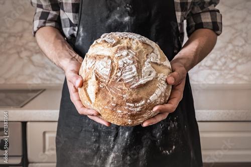Fotografie, Obraz  Hands of man holding big loaf of white bread