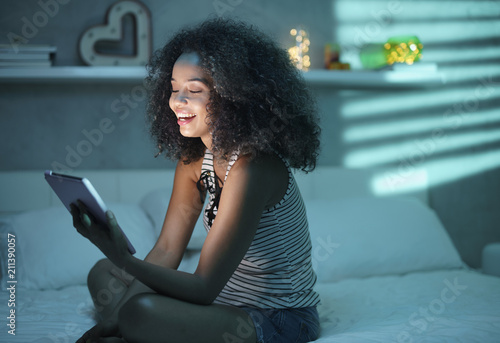 Fotografie, Tablou  Hispanic Girl Watching Film With Tablet And Laughing