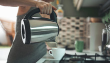 Close Up Focus On Female Hand Holding Kettle And Pouring Water Into Cup. Lady Is Preparing Morning Hot Drink For Breakfast In Kitchen. Copy Space In Right Side