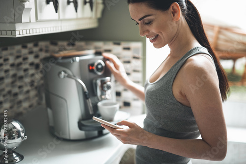 Fotografiet Side view of smiling attractive woman standing by coffee machine with smartphone in hands