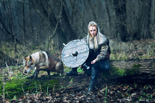 Plakát  Scandinavian northern viking with wolf, ax and shield in hand looking threateningly