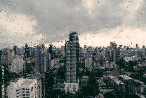 Rain over Bangkok: Out of focus cityscape behind the window glass with rain drops Fototapeta