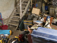 Old Dingy Residential Unfinished Basement Cluttered With Storage Of Random Things