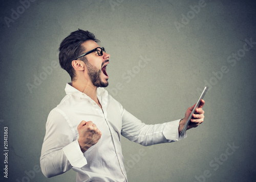 Fotografía Cheerful hipster man holding tablet and fist up while screaming with happiness