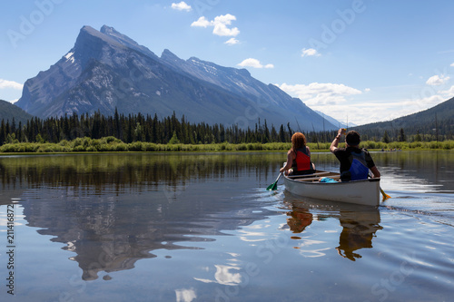 Fotografie, Obraz  Couple adventurous friends are canoeing in a lake surrounded by the Canadian Mountains