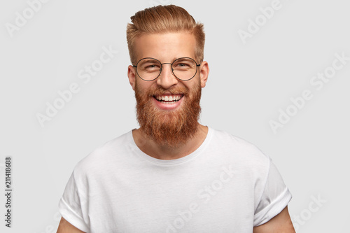 Fototapeta People, youth, positiveness concept. Happy male with long thick ginger beard, has friendly smile, rejoices having day off for his hobby, expresses happiness, stands alone against white wall. obraz