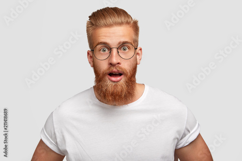 Fototapeta Emotional hipster with stupefied expression, wonders latest news, has thick red beard and mustache, stares at camera, can`t believe his eyes, wears casual white t shirt and round spectacles. obraz