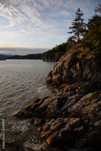 In de dag Kust Rocky coast on the ocean viewed from Lighthouse Park during a vibrant sunset. Located in Horseshoe Bay, West Vancouver, BC, Canada.