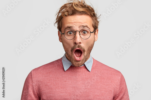 Stressed hipster male has shocked expression, realizes that his car is stolen, keeps mouth widely opened, stares through round spectacles, isolated over white background Canvas Print
