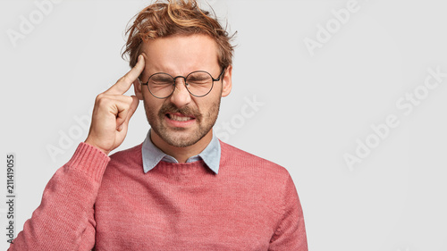 Obraz Photo of stressed male feels pressure as being overworked, keeps index finger on temple, has headache, frowns face, isolated over white background with copy space for your advertising content - fototapety do salonu