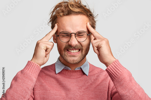 Obraz Miserable male clenches teeth from tiredness and pressure on work, keeps index fingers on temples, wears sweater, tries to gather with thoughts, isolated over white studio wall. Facial expressions - fototapety do salonu