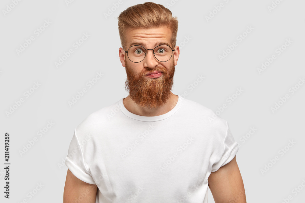 Fototapeta Handsome bearded male purses lips with hesitation, being surprised and puzzled to recieve unexpected news, dressed in casual white t shirt, poses against studio background. Trendy hipster indoor