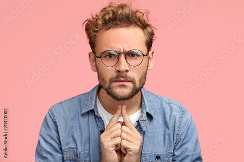 Fototapeta Headshot of serious intelligent young male proffesor listens something with atte