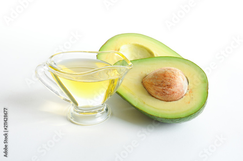 Gravy boat with oil and ripe fresh avocado on white background