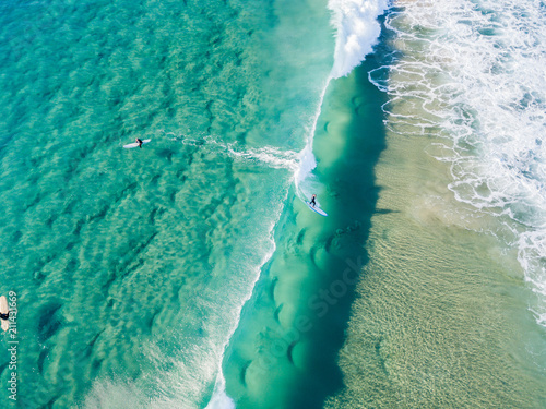In de dag Olijf An aerial view of surfer riding a wave waiting at the beach on the Gold Coast in Queensland Australia