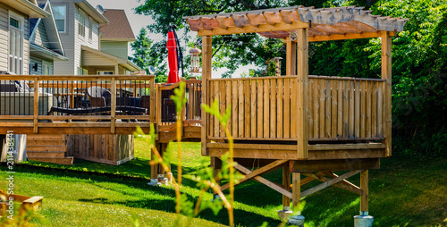 Fotografie, Tablou Raised backyard wooden deck and gazebo behind a row of houses