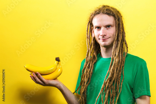 Fotografie, Obraz  Happy young man holding bananas on a yellow background