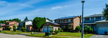 Panorama Of A Row Of Residential Houses Along A Street, One With Solar Panels On The Roof