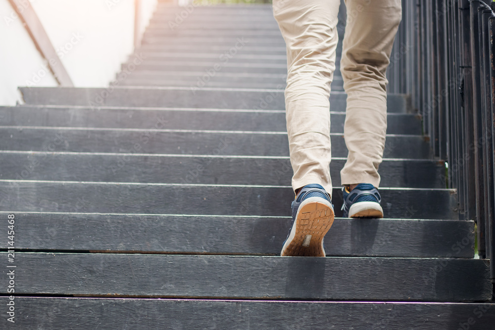 Fototapeta Young man walking up the stairs with sun sport background.step for success.