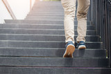 Young man walking up the stairs with sun sport background.step for success.