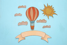 Hot Air Balloon, Space Elements Shapes Cut From Paper And Painted Over Wooden Blue Background.