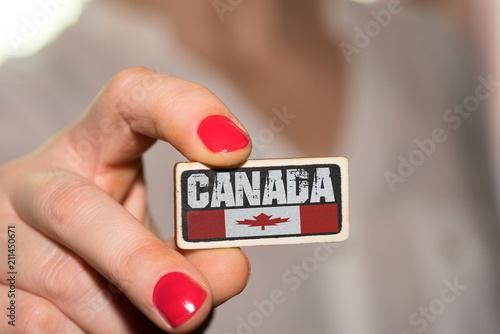 Spoed Foto op Canvas Canada Eine Frau und ein Schild mit dem Aufdruck Kanada und der kanadischen Nationalfahne