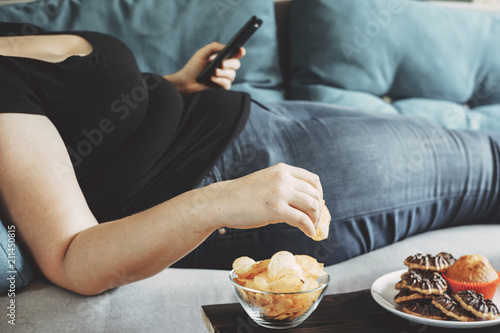 g, sedentary lifestyle, compulsive overeating. Obese woman laying on sofa with smartphone eating chips