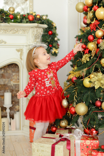 Little girl wearing red dress decorating Christmas tree near fireplace and gifts. Concept fo New Year atmosphere and children celebrating winter holidays.