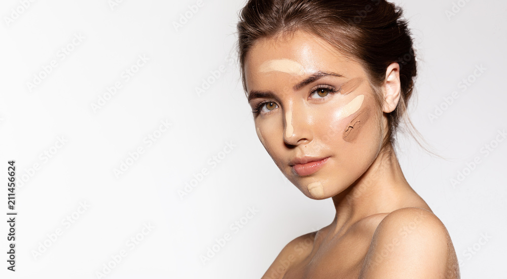 Fototapeta Waist up portrait of engaging young woman with cosmetic tonal foundation on her face. Glorious brunette looking at camera with calmness. Beauty treatment concept