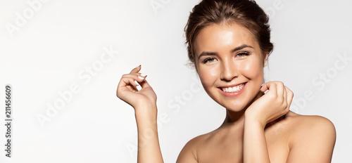 Fototapeta premium Portret pięknej młodej kobiety w pasie z czarującym uśmiechem. Radosna brunetka z naturalnym makijażem patrząc w kamerę z radością i szczęściem. Na białym tle na szarym tle