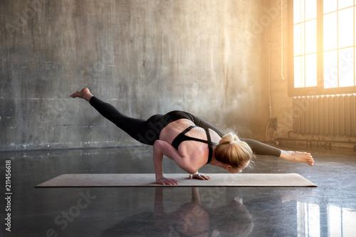 Fotografie, Obraz  Modern girl doing yoga asana in a light sunny loft class