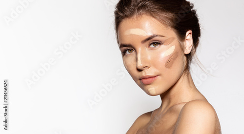Waist up portrait of engaging young woman with cosmetic tonal foundation on her face Fototapet