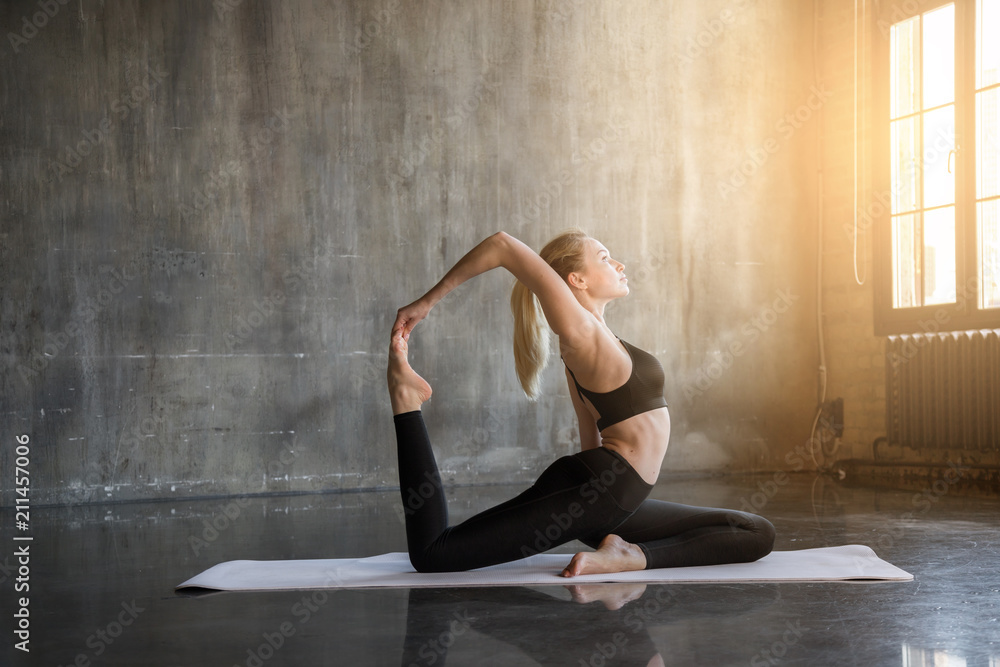 Fototapeta Young woman doing ashtanga yoga practice in a loft studio, surrounded by bright sunlight. Beutiful girl meditating makes herself a healthy body and strengthening the spirit. - obraz na płótnie